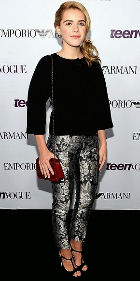 PrintedPants- Kiernan Shipka wore a gorgeous pair of brocade pants, a cape-like black top, and strappy platforms by Emporio Armani with a red Swarovski cross-body bag.